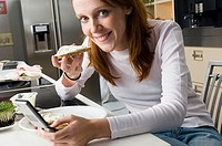 Portrait of a young woman holding a slice of bread and operating a mobile phone