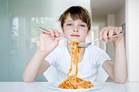 Portrait of a boy holding noodles with a fork and a spoon