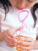 Girl drinking juice with straw