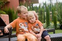 Two brothers, 4 and 2, sitting toether on a chair