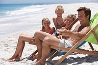 Family relaxing in deckchairs on beach, father taking photograph with camera, smiling, side view