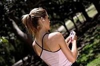Woman standing in park, listening to MP3 player, rear view, trees in background tilt