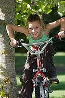 Girl 7-9 sitting on bicycle beside tree in garden, leaning forwards, smiling, front view, portrait