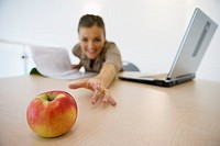 Businesswoman sitting in office with laptop and document, reaching for red apple on desk, smiling, focus on foreground, surface level