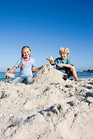 Boy 4-6 and girl 6-8 building sandcastles on sandy beach, smiling, front view, portrait