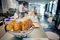 Waiter working behind counter in cafe, focus on basket of croissants in foreground, close-up