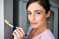 Woman decorating at home, painting wall with paintbrush, smiling, close-up, side view, portrait