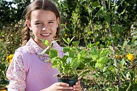 Girl 9-11 holding pot plant in garden, smiling, close-up, portrait
