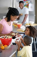 Two generation family preparing food at home, mother serving fruit salad to children 6-9