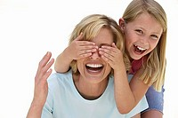 Girl 9-11 covering mother´s eyes with hands, laughing, front view, portrait