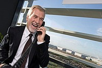 Mature businessman using telephone in office, standing beside large window, laughing tilt