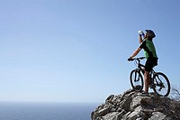 Male mountain biker sitting on bicycle at edge of rock, looking at horizon over sea, rear view