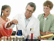 Teenagers 15-17 doing science experiment at desk in classroom, teacher assisting, smiling