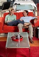 Couple testing new red sofa in furniture store, woman sitting with feet up on man´s lap, smiling