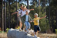 Two generation family walking in line on log, arms outstretched, smiling