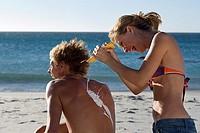 Teenage girl 17-19 squirting sun cream on boyfriend´s back at beach, laughing, rear view