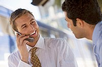 Two businessmen talking, one man using mobile phone, smiling