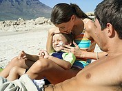 Family relaxing on beach, boy 4-6 sitting in mother´s lap, woman applying suncream to son´s face, side view