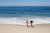 Boy and girl 5-7 holding hands on sandy beach near water´s edge, Atlantic Ocean in background, rear view