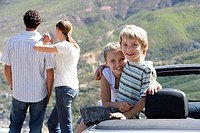 Couple looking at mountain scenery, two children 6-9 sitting in parked convertible car at roadside, smiling, portrait