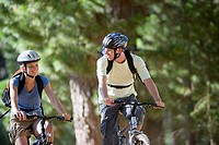 Couple, with rucksacks and cycling helmets, mountain biking on woodland trail, smiling