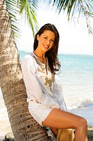 Beautiful young woman wearing all white, leaning against a palm tree