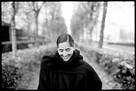 Smiling woman walking down alley of trees in public Paris garden