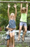 Young girl helping other girl onto horizontal pole
