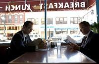 Two men in suits and glasses look at diner menus
