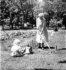Elderly woman gardening with child, circa 1930´