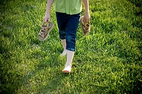 Young girl walking barefoot in grass, holding sandals