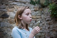 Young girl blows on dandelion