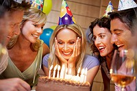 Woman Blowing out Candles on Birthday Cake