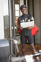 Bicycle courier standing outside building