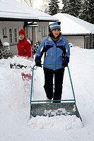Mother and daughter plowing snow with snow pushers in Espoo, Finland