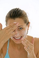 Portrait of a young woman applying soap to her face