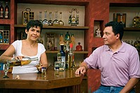 Female bartender pouring tequila into a glass with a mature man sitting at a counter in a cafe