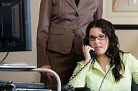 Businesswoman talking on a phone with a businesswoman standing behind her