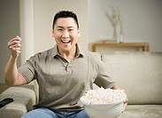 Asian man smiling on sofa with popcorn
