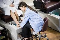 Asian nail technician filing clientÆs toenails