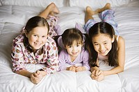Portrait of three girls laying on bed