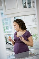 Pregnant African woman looking at medication