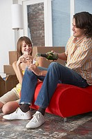 Couple with champagne in house with red chair celebrating