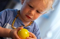 baby playing concentrated with yellow ball