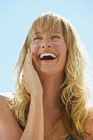 Closeup of woman applying sunblock to cheeks laughing