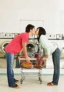 Asian couple kissing in laundromat