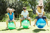 Girls and boy playing on beach balls outdoors