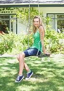 Teenage girl on swing outdoors in yard
