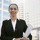 Hispanic businesswoman holding paperwork