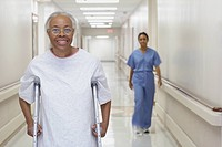 Senior African woman walking on crutches in hospital corridor